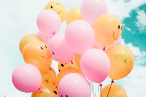 Pink and orange balloons with smiley faces