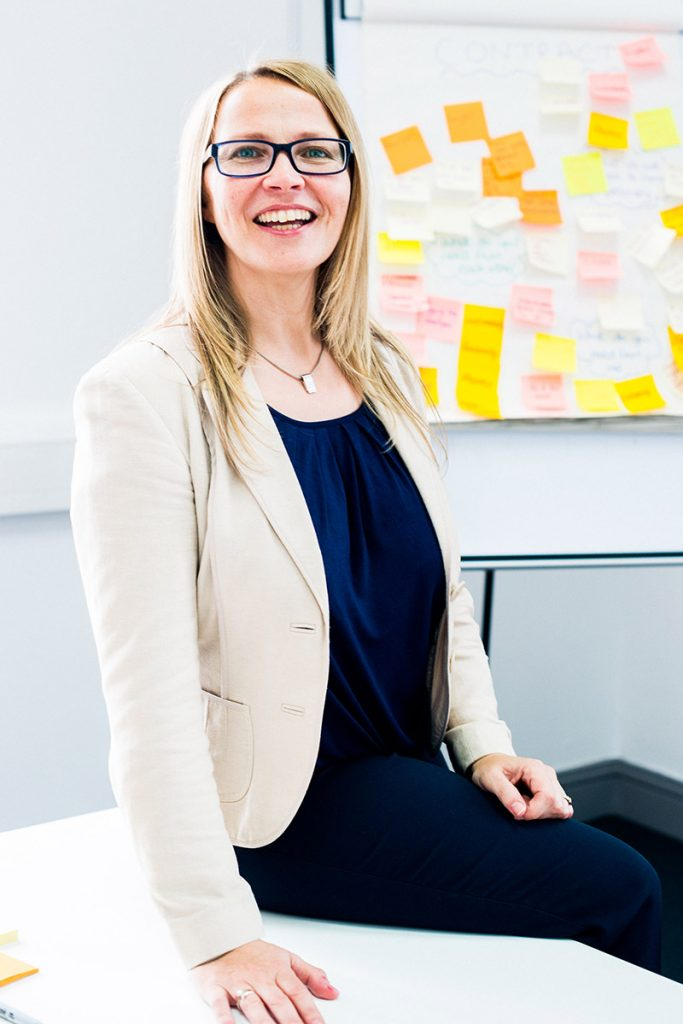 Andrea Goodridge sat on a desk - Ad Florem