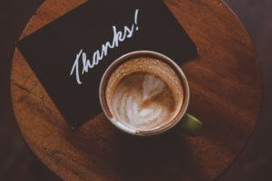 Cup of coffee and note saying thanks to symbolise gratitude